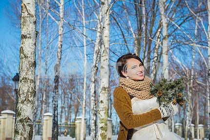Beautiful bride on a sunny winter day behind the birch. snowy weather. blye sky and trees on the background. Girl in a short wedding dress, rustic style smiling