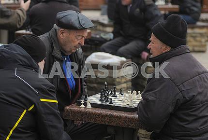 Elderly people play chess