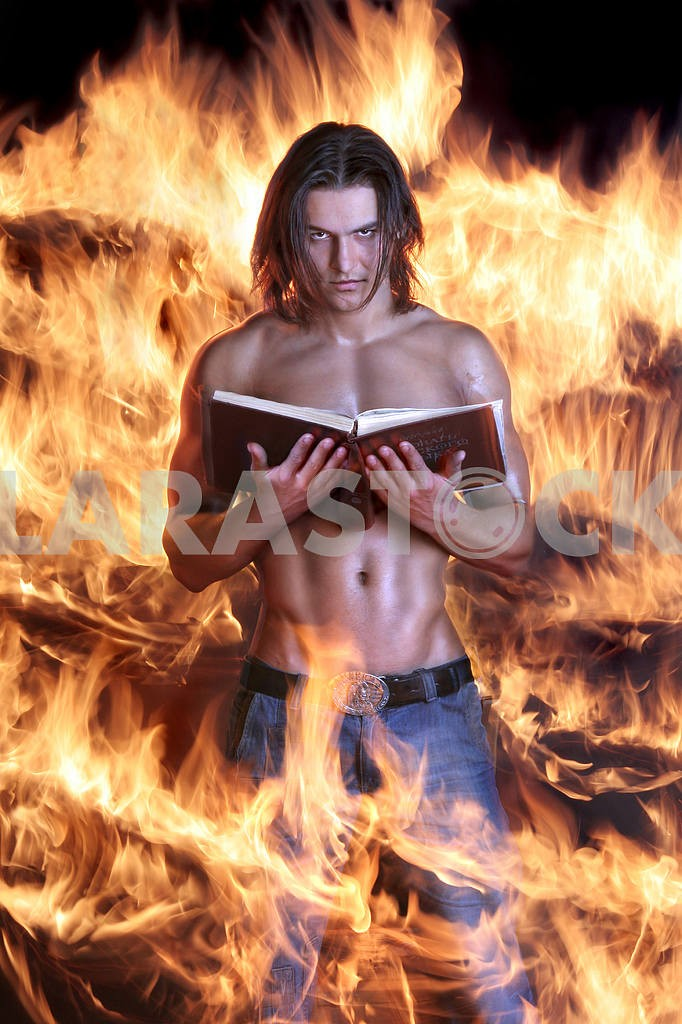 Brawny the man holds the book and burns on fire — Image 5317