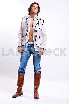 Man in a white shirt, jeans and boots. Denuded torso
