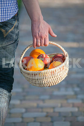 male hand holding a basket with red apples