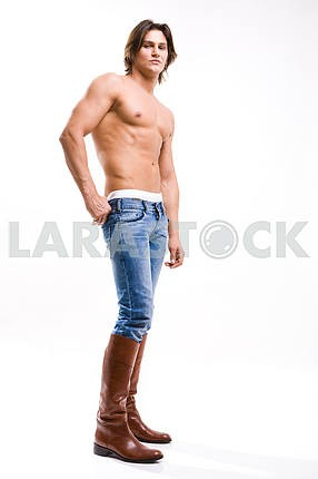 Fashion shot of a Young Man in a jeans and boots. Denuded torso