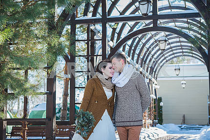 Wedding couple in a showy wither day, walking, having fun behind the pine-tree. rustic style  short wedding dress. Girl brunette. beautiful bride winter lanscape on the background