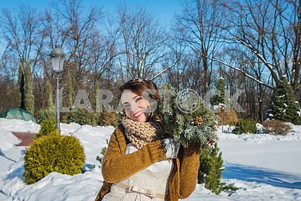 Happy beautiful bride in a snowy winter day. Sunny weather. stylish. with the wedding bouquet made from pine-tree hand made. mittens on hands, short wedding dress. rustic style