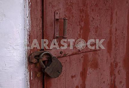 Деревянные двери закрыты висячим замком