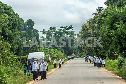 Women walk along the road to Zanzibar