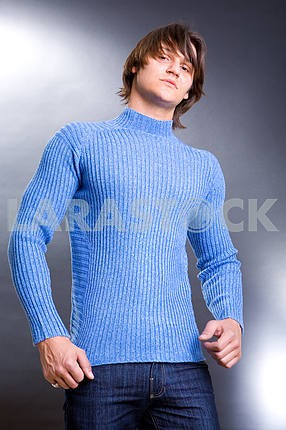 Young men dressed in modern clothes. Sweater of blue colour.