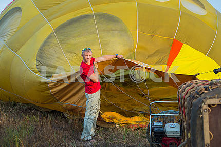 Preparing the baloon. hot air. big baloon. flight. come fly with me. in the field.  yellow baloon. summer fun. a men holding baloon before the flight