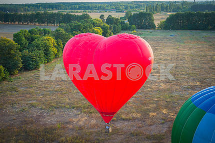 a view from high above - landsacape. little town and the horisont. Balloon flight. basket 1000 meters. having fun, romantic flight and a big heart shape baloon