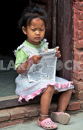 The girl is reading a newspaper.