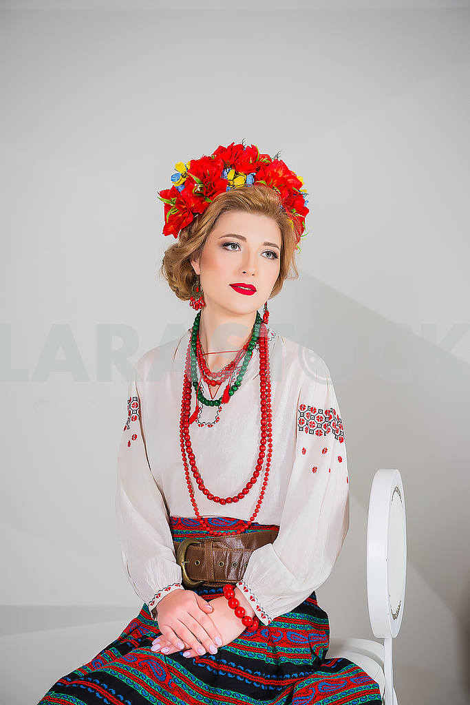 A beautiful girl in National Ukrainian Costume. captured in studio. Embroidery and jacket. wreath. circlet of flowers. red lips — Image 54309