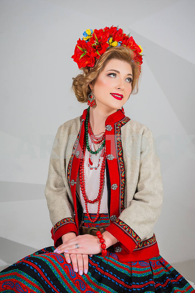 A beautiful girl in National Ukrainian Costume. captured in studio. Embroidery and jacket. wreath. circlet of flowers. red lips — Image 54316