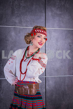 A beautiful girl in National Ukrainian Costume. captured in studio. Embroidery and jacket. wreath. red lips. light. historical costume. Nationality - ukrainian