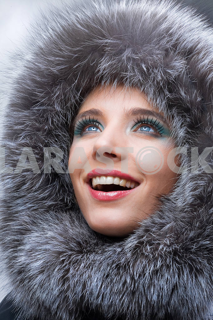Portrait of the beautiful, smiling young woman with a fur hood. — Image 5473