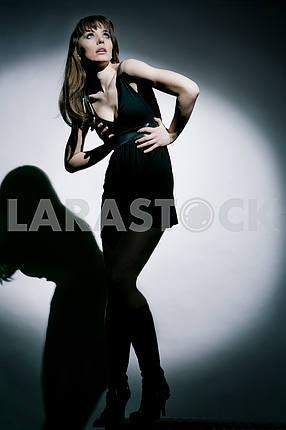 Girl in a black dress. In all growth. Looks in a distance.