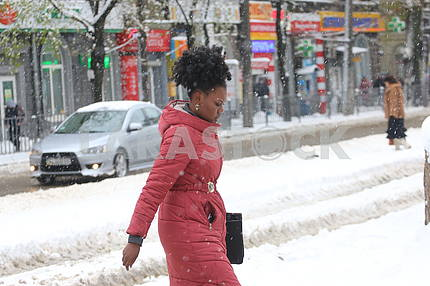 A woman is walking on a snow-covered street