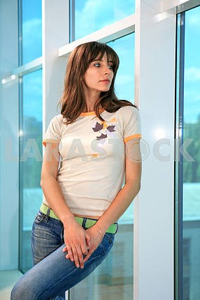 Young woman leaning against glass wall