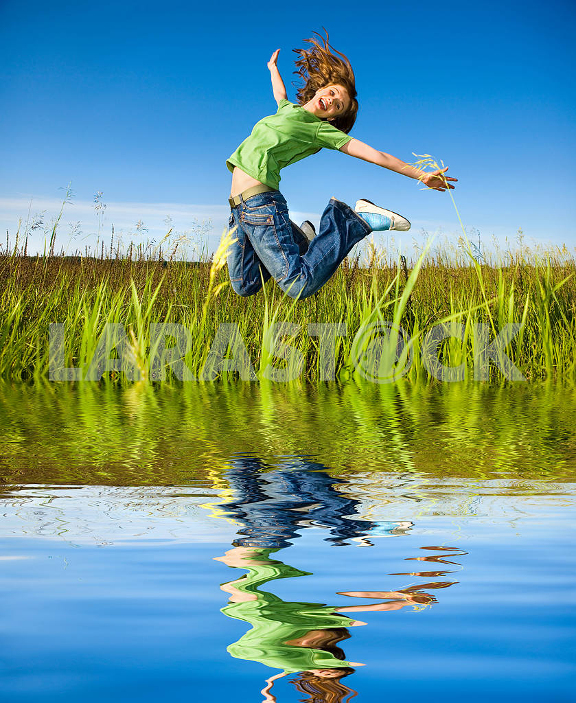 Happy young woman is jumping in a field — Image 5509