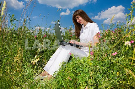 Young woman on the grass field with a laptop
