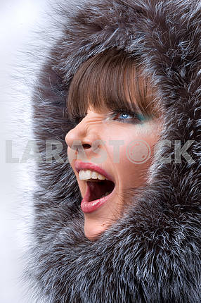 Portrait of the beautiful, shouting young woman with a fur hood