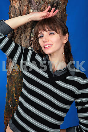 Portrait young woman standing near a tree. At the blue backgroun