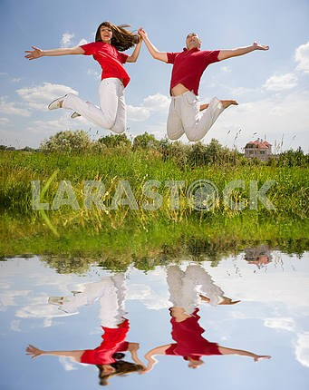 Happy Young love Couple - jumping under blue sky. Reflected in w