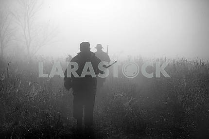 Silhouettes of hunters in the fog