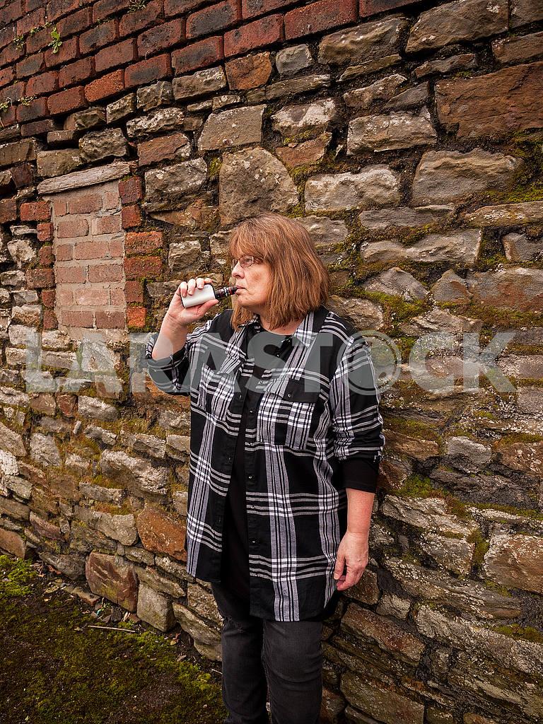 Зрелая женщина курит электронную сигарету — Изображение 56084