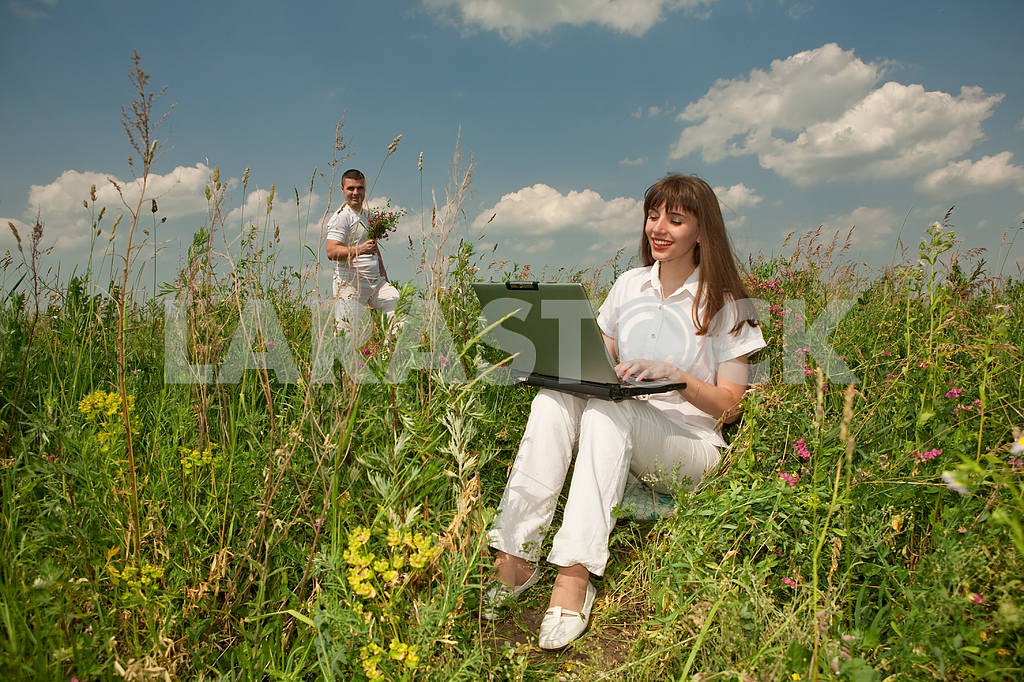 Happy Young Woman on the grass field with a laptop against the b — Image 5642