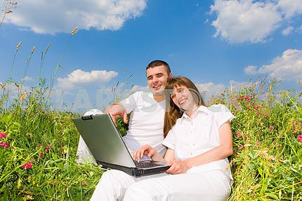 Young couple sitting on the grass field with a laptop. Against t