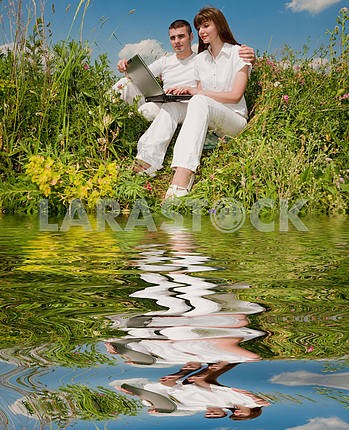 Casual happy couple on a laptop computer outdoors. Reflected in