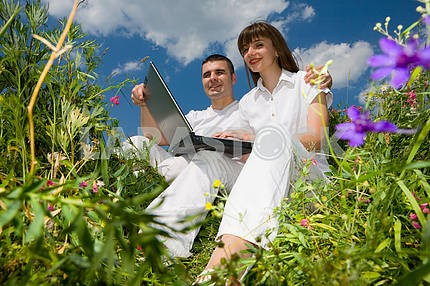 Young couple sitting on the grass field with a laptop