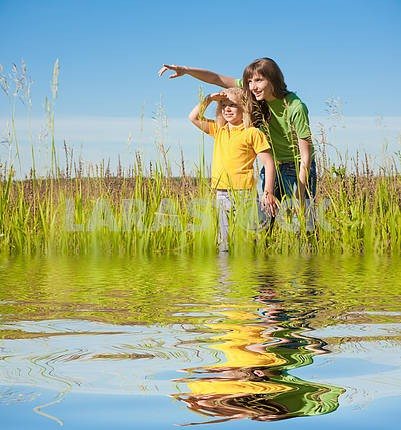 Happy mother and daughter on field. Reflected in Water.
