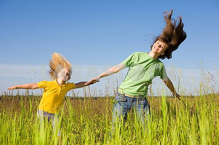 Happy woman and girl making exercises on field.