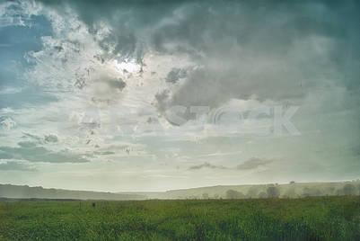 Проливной дождь в долине на фоне холмов