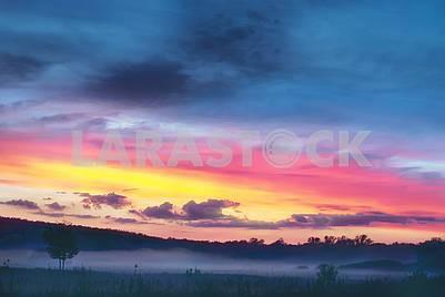 Прекрасный красочный закат в холмистой долине