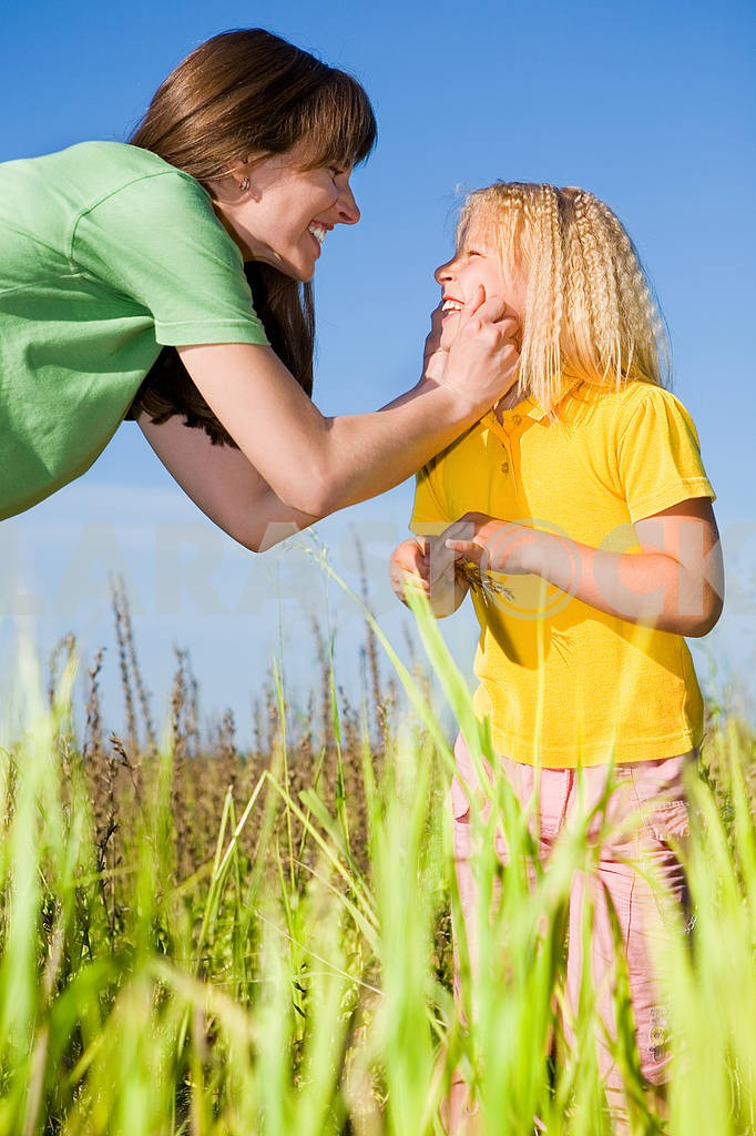 Happy mother and daughter laughing on field — Image 5741