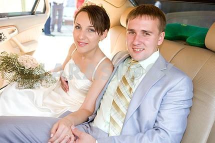 Portrait smiling groom and bride in wedding car