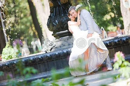 Groom and bride joy against backdrop fountain