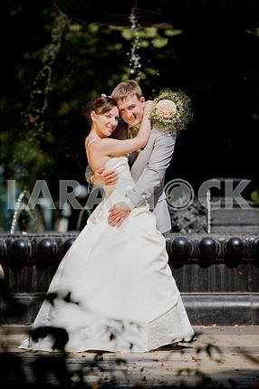 Groom and bride joy against backdrop fountain. In all growth.