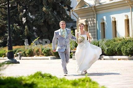 Groom and bride runinng