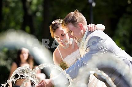 Groom and bride joy in fountain
