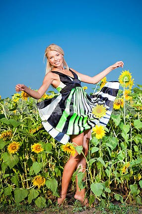 Happy young woman in a field of sunflowers