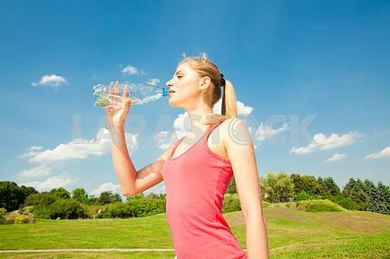 Красивая девушка питьевой воды против голубого неба