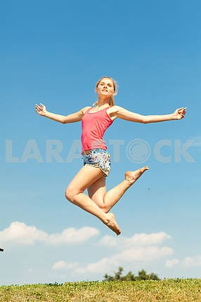 Happy young women jumping in field