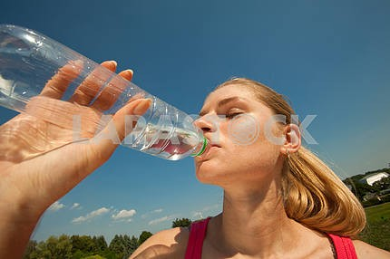 Beautiful girl drinking water against blue sky
