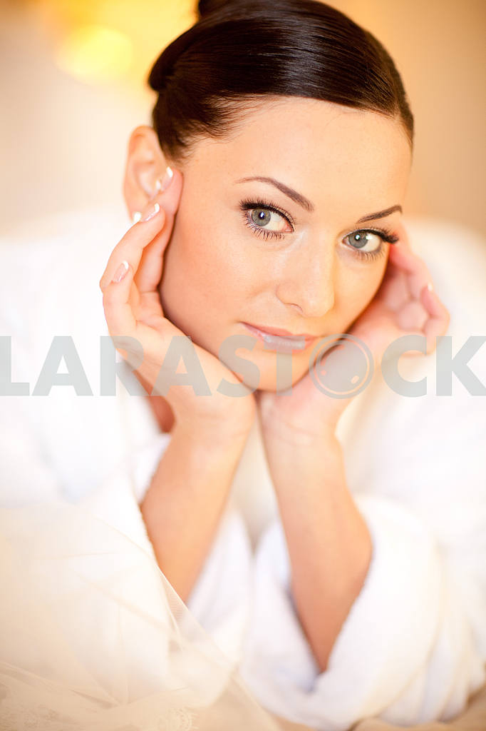 Beautiful girl in a white coat lying on the bed — Image 5960