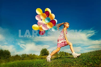 Teen girl with balloons is fun on green grass