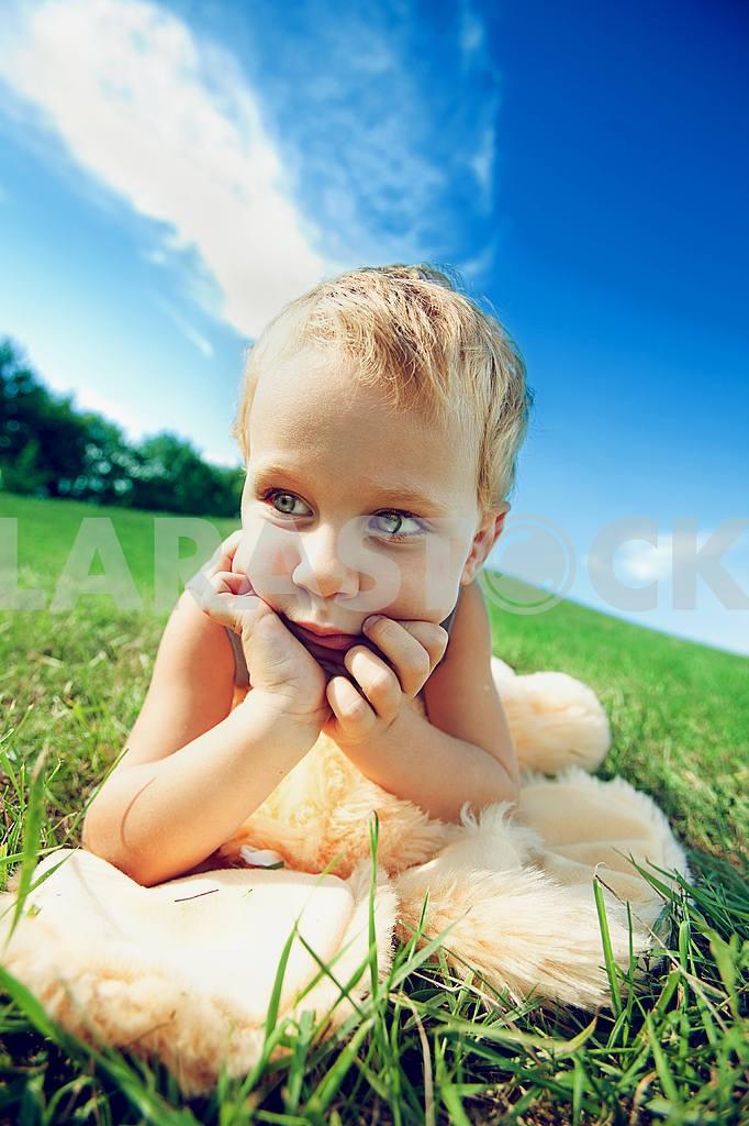 Little boy lying on green grass — Image 6003