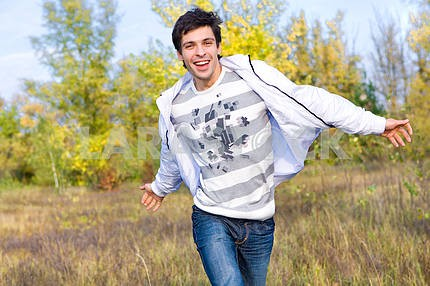 Happy young man jumping against background of sky and trees